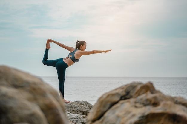 Mujer entrenando yoga en la playa por la mañana.yoga, fitness y concepto de estilo de vida saludable