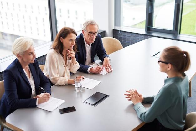 Mujer durante la entrevista de trabajo y tres elegantes miembros de la dirección