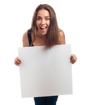 Mujer entusiasmada mostrando un cartel en blanco