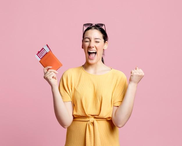 Mujer entusiasta gritando mientras sostiene un pasaporte