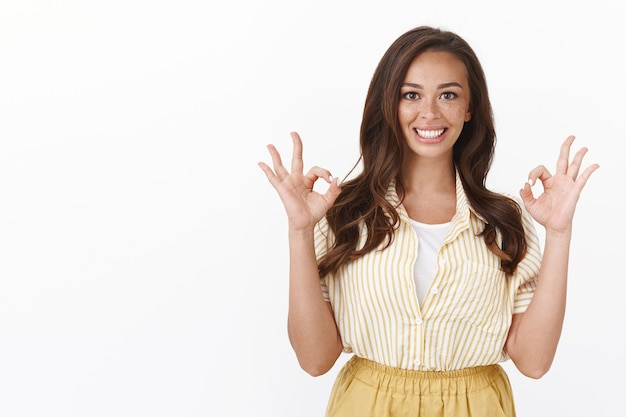 Mujer entusiasta que muestra un gesto bien, ok, una sonrisa que se siente excelente, recomendar un producto la ayudó mucho, sonreír encantada, dar aprobación, como su elección, de pie en una pared blanca de apoyo