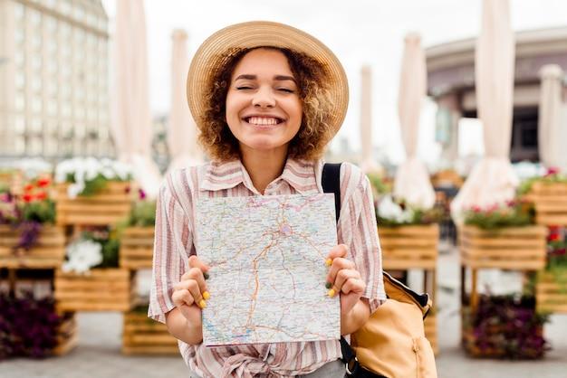 Mujer entusiasta que viaja sola sosteniendo un mapa