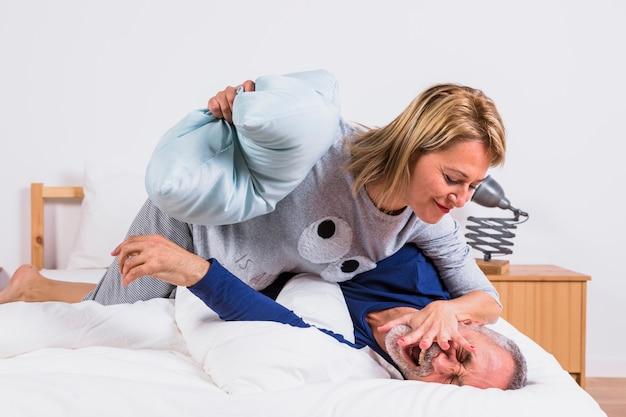 Mujer envejecida en el hombre que se divierte con las almohadas y que miente en cama
