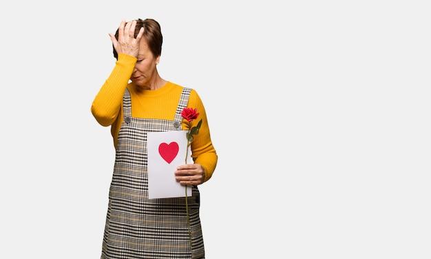 La mujer envejecida media que celebra el día de tarjetas del día de san valentín olvidadiza, realiza algo