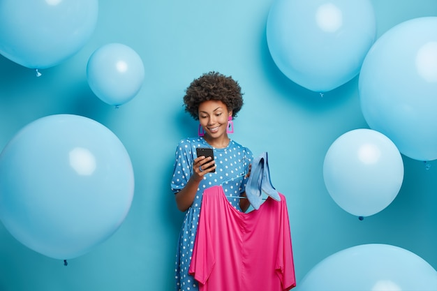 Mujer envía mensajes de texto a través de un teléfono inteligente tiene vestido rosa en la percha y zapatos de tacón se prepara para una ocasión especial aislado en azul