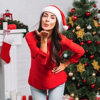 Mujer enviando beso al aire cerca de arbol de navidad