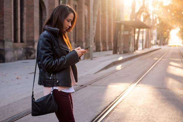 Mujer enviando mensajes de texto por teléfono mientras cruza la calle