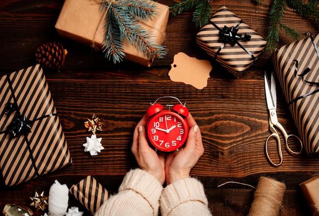 Mujer envolviendo un reloj despertador como regalo en una mesa