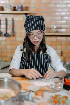 Mujer envuelta en albóndigas cocinero de comida asiática.