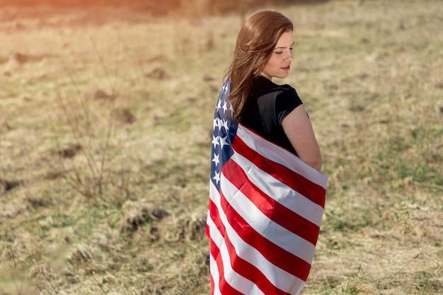 Mujer envuelta en bandera americana en campo