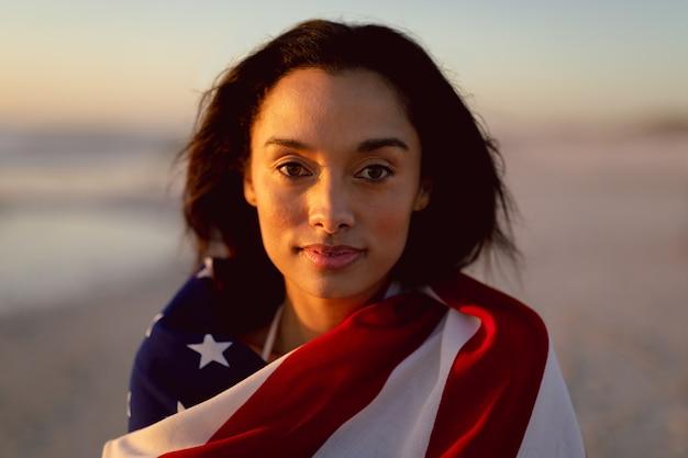 Mujer envuelta en la bandera americana de pie en la playa
