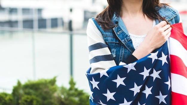Mujer envuelta en gran bandera americana
