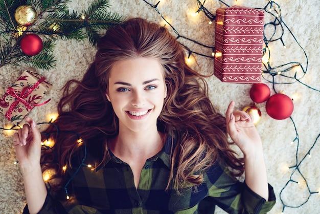 Mujer envuelta en luces de navidad en el suelo
