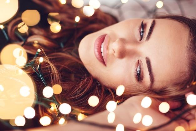 Mujer envuelta en luces de navidad