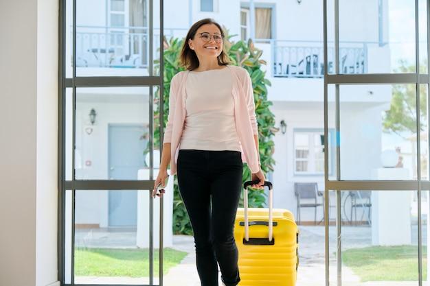 Mujer con equipaje entrando en el lobby de un hotel