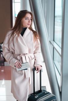 Mujer con equipaje esperando su vuelo.