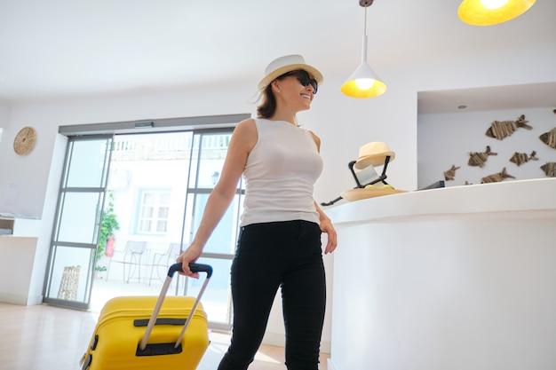 Mujer con equipaje en el lobby de un hotel