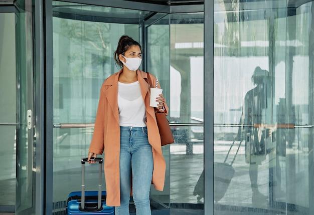 Mujer con equipaje y máscara médica en el aeropuerto durante la pandemia