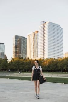 Mujer con equipaje en el parque urbano de tiro largo