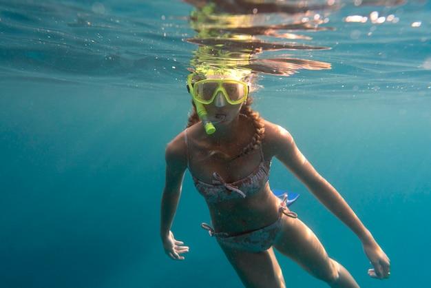 Mujer con equipo de buceo nadando en el océano