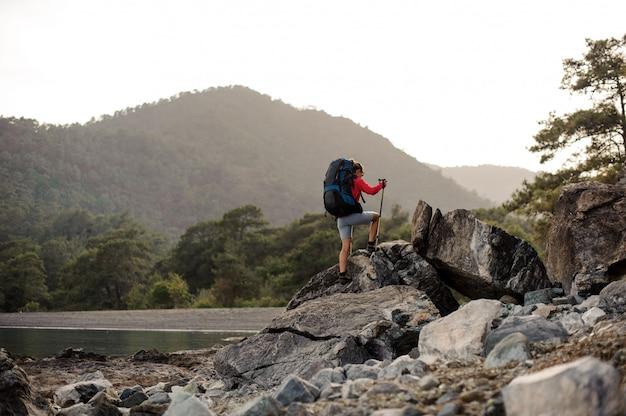Mujer con equipo de senderismo caminando por la costa pedregosa