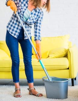 Mujer con equipos de limpieza en la sala de estar.