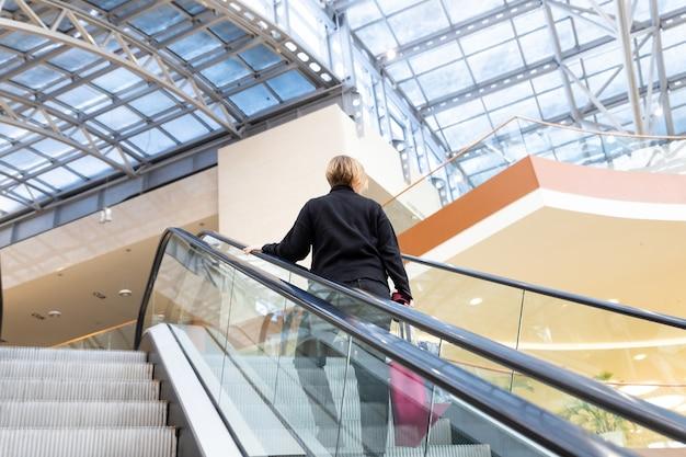Mujer en la escalera mecánica en el centro de negocios vista trasera de la mujer mientras usa las escaleras mecánicas en el centro comercial