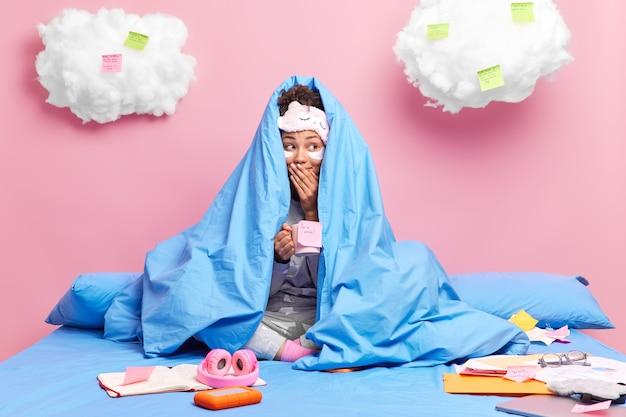 La mujer se esconde debajo de una manta suave bebe café se aplica parches debajo de los ojos para reducir las arrugas siéntate en una cama cómoda trabaja ríe silenciosamente hace tareas en el dormitorio