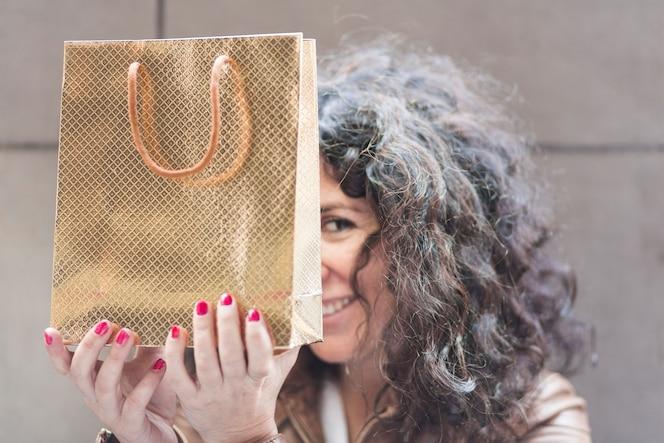 Mujer escondida con bolsa de compras