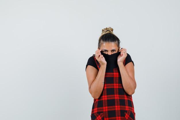 Mujer escondiendo el rostro detrás de su cuello con vestido delantal y mirando asustado, vista frontal.