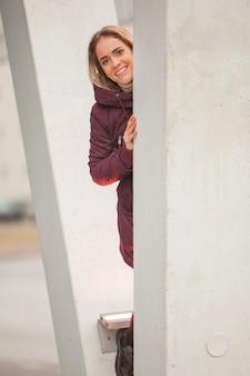 Mujer escondiéndose detrás de pilar