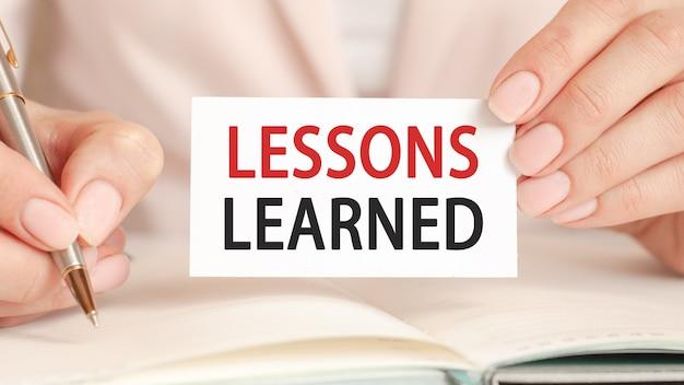 La mujer escribe en un cuaderno con un bolígrafo plateado y una tarjeta con texto: lecciones aprendidas. fondo rosa. concepto de educación y negocios.