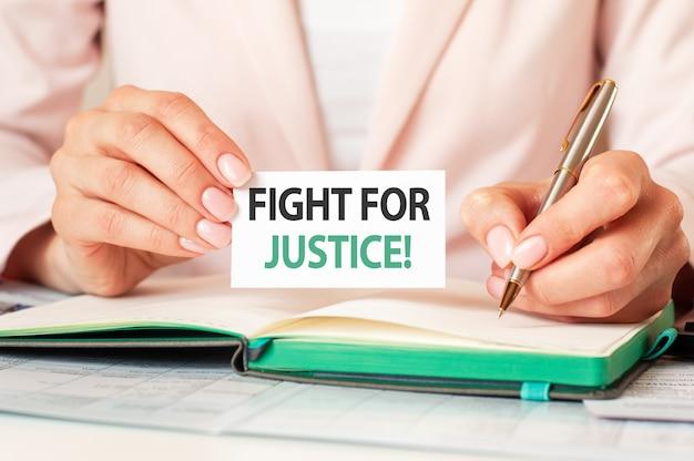 Mujer escribe en un cuaderno con un bolígrafo plateado y una tarjeta con el texto: lucha por la justicia