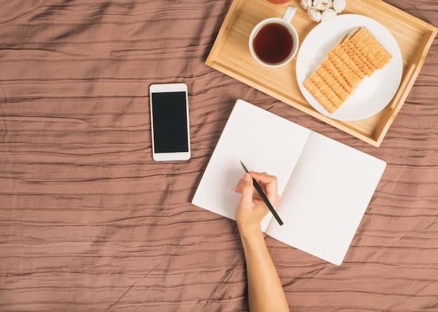 La mujer escribe en un gran cuaderno abierto de color blanco, yace en la cama con un teléfono inteligente, bandeja de desayuno