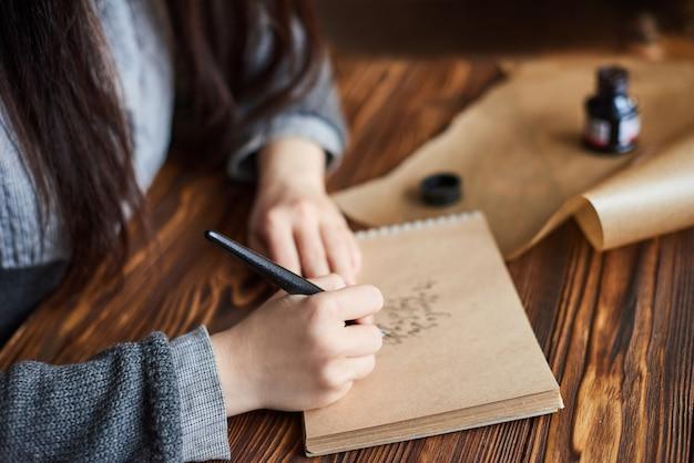La mujer escribe con la pluma de tinta texto de escritura caligráfica en papel artesanal