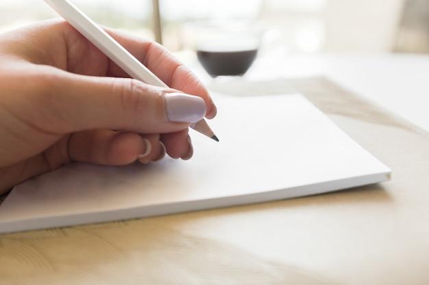 Mujer escribiendo en el bloc de notas