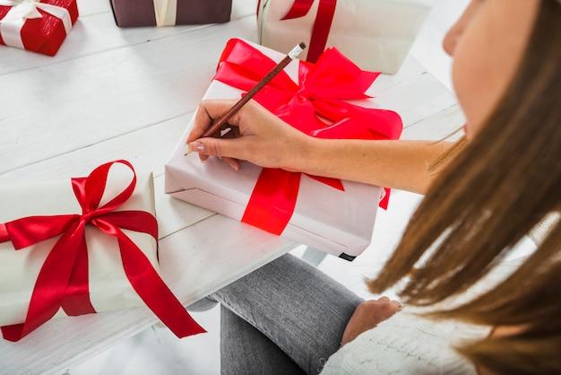 Mujer escribiendo en caja de regalo