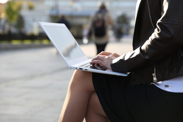 Mujer escribiendo en la computadora portátil al aire libre cerrar