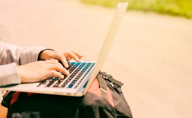 Mujer escribiendo en la computadora portátil colocada en las mochilas