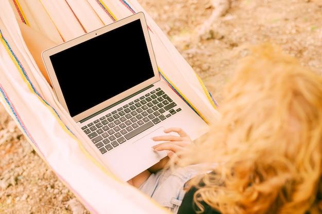 Mujer escribiendo en la computadora portátil en hamaca
