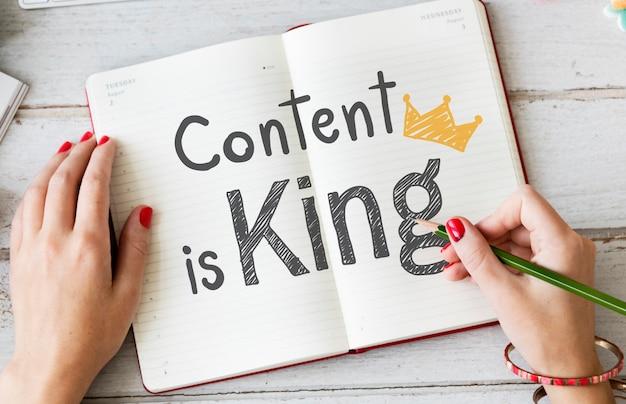 Mujer escribiendo contenido es rey en un cuaderno
