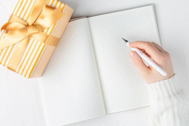 Mujer escribiendo en un cuaderno en blanco entre caja de regalo. endecha plana, vista superior