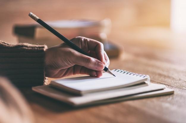 Mujer escribiendo en cuaderno en blanco sobre mesa de madera