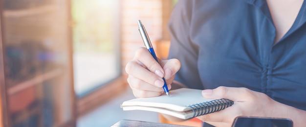 La mujer está escribiendo en un cuaderno con un bolígrafo en la oficina. banner web.