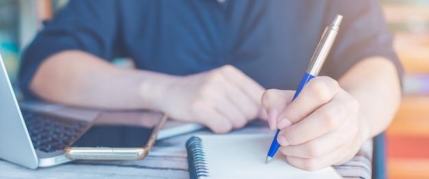 La mujer está escribiendo en un cuaderno con un bolígrafo y está utilizando un teléfono móvil en la oficina. banner web.