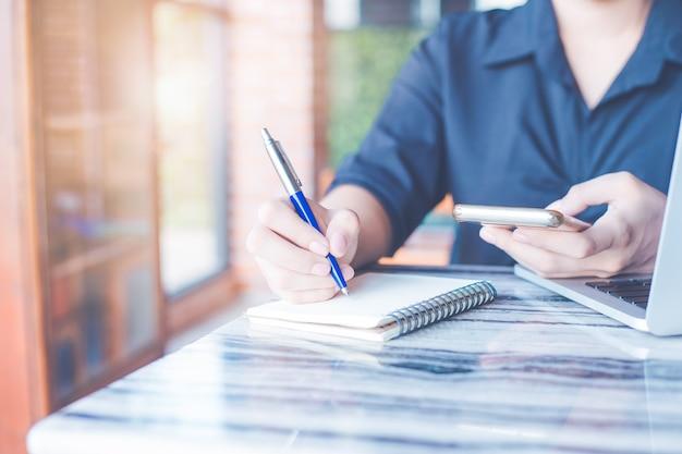 La mujer está escribiendo en un cuaderno con un bolígrafo y está utilizando un teléfono móvil en la oficina.