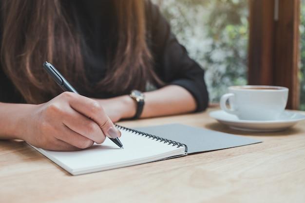 Una mujer está escribiendo en un cuaderno y una taza de café en la mesa de madera