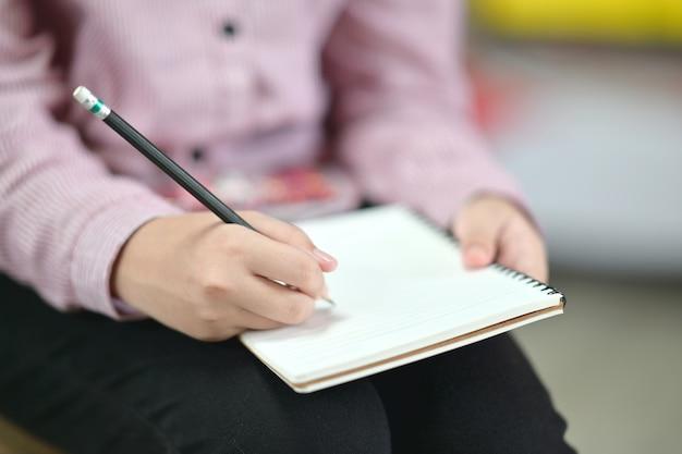 Mujer escribiendo en el cuaderno.