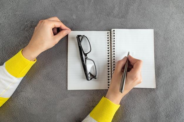 La mujer está escribiendo en el cuaderno.