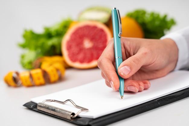 Mujer escribiendo y fruta borrosa